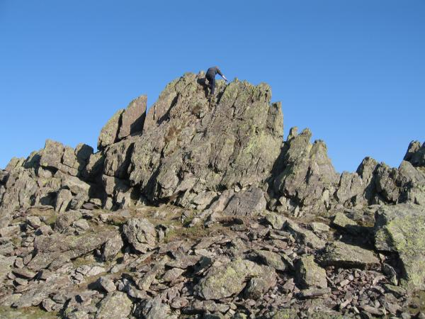 A walker attempting to down climb the summit of Helm Crag