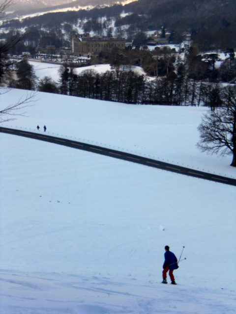 Rachel heads down the hill with Chatworth House in the b