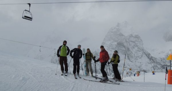 Mathias, Jon, Laetitia, Pete, and Rebecca at Courmayeur with the impressive Italian face of Mont Blanc emerging from the clouds behind.