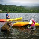 Paul teaching Pete how roll a kayak on Coniston Water with Phil watching on