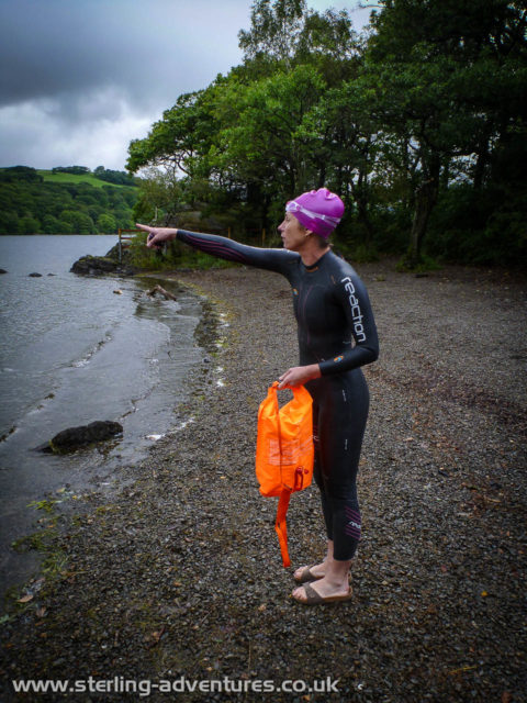 """Laetitia pointing out in to Consiton Water, """"we should swim to there!.  As if it's possible to point at some arbitrary spot of a completely scary and featureless body of water!"""