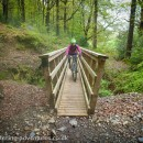 Laetitia crosses a bridge on the North Face Trail in Grisedale Forest